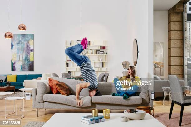 Couple in modern furniture store doing headstand on couch