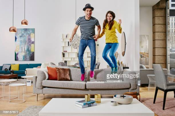 Couple in modern furniture store jumping on couch