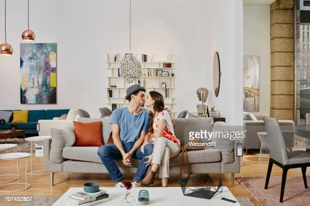 Couple in modern furniture store sitting on couch, kissing