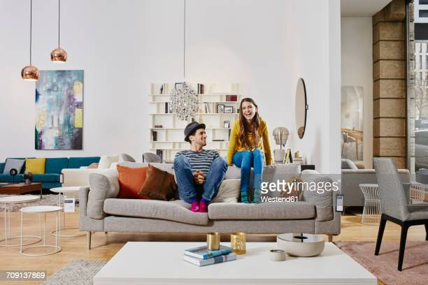 couple in modern furniture store sitting on couch, laughing - sofa stock-fotos und bilder