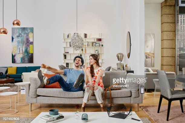 Couple in modern furniture store testing couch, being happy