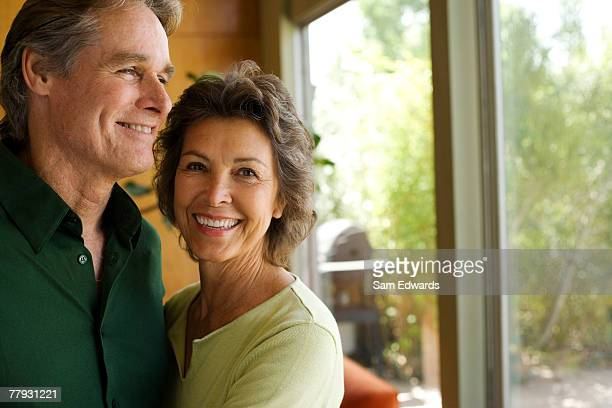 couple in modern home by large window - 50 54 years stock pictures, royalty-free photos & images