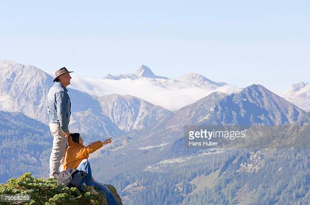 'Couple in mountains, watching summits'