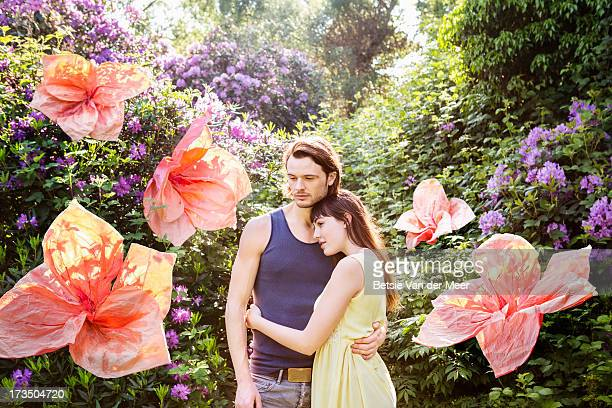 Couple in nature,surrounded by large flowers.