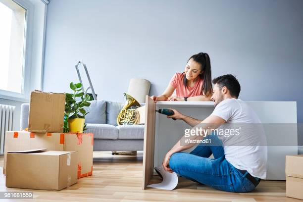 couple in new apartment assembling furniture together - estante muebles fotografías e imágenes de stock
