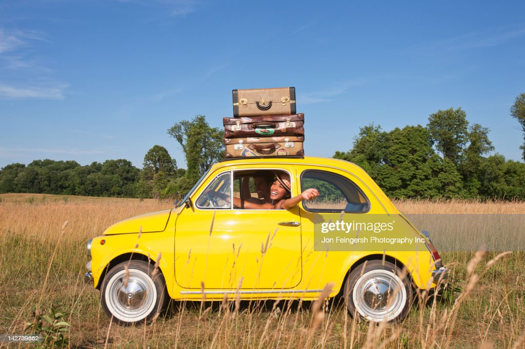 Couple in old-fashioned car on road trip : Stockfoto