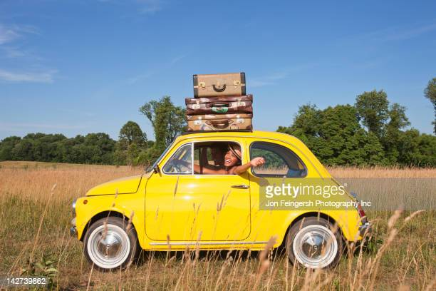 couple in old-fashioned car on road trip - yellow photos et images de collection