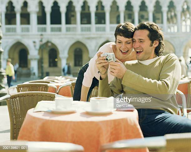 Couple in outdoor cafe looking at camera, smiling