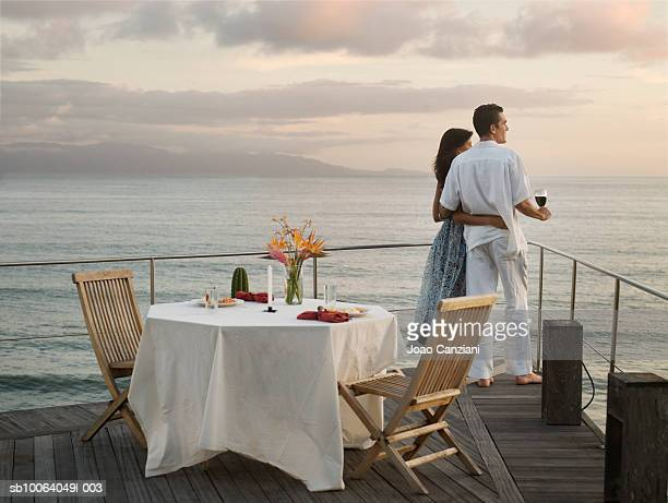 Couple in outdoor restaurant, embracing and looking at sea, side view