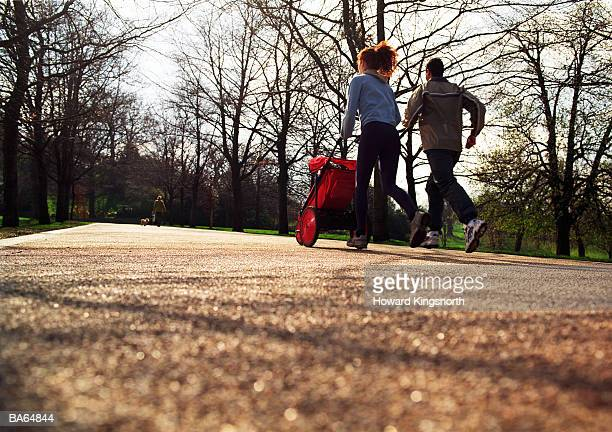 couple in park jogging with pushchair, rear view - three wheeled pushchair stock pictures, royalty-free photos & images
