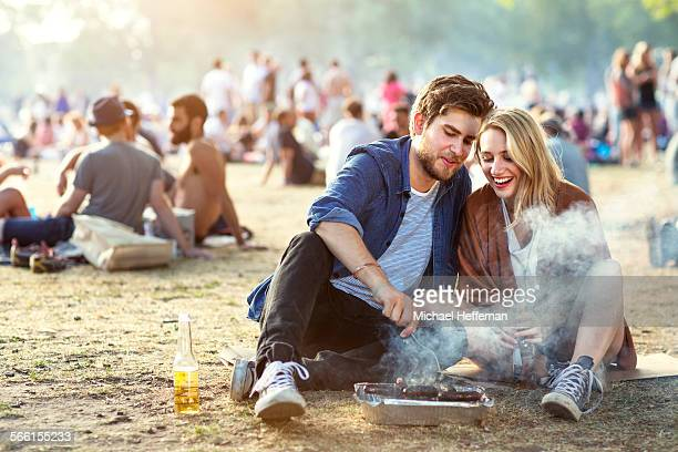 Couple in park using barbecue
