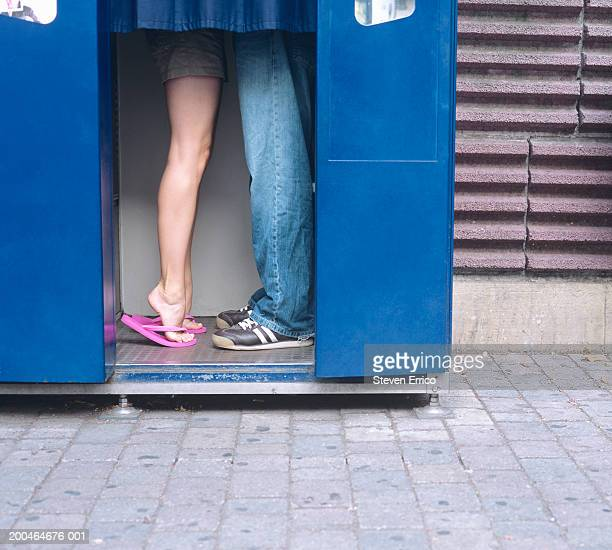 Couple in photo booth kissing, low section