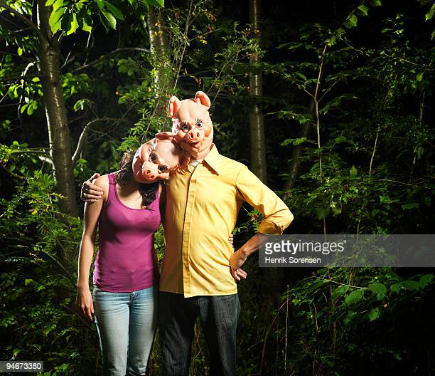 Couple in pig masks in forest embracing