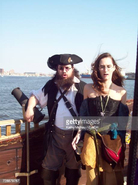 Couple In Pirate Costume Standing In Ship Against Clear Sky