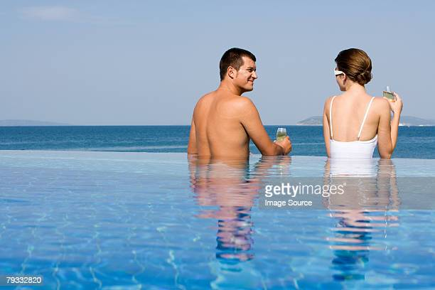 Couple in pool with champagne