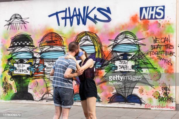 Couple in protective face masks is seen kissing in front of Coronavirus themed graffiti at Oxford Street as Coronavirus lockdown eases in London,...