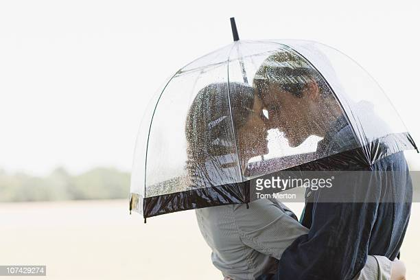 Couple in rain hugging underneath umbrella