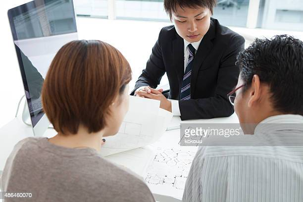 couple in real-estate agency talking to construction planner - real estate office stock photos and pictures