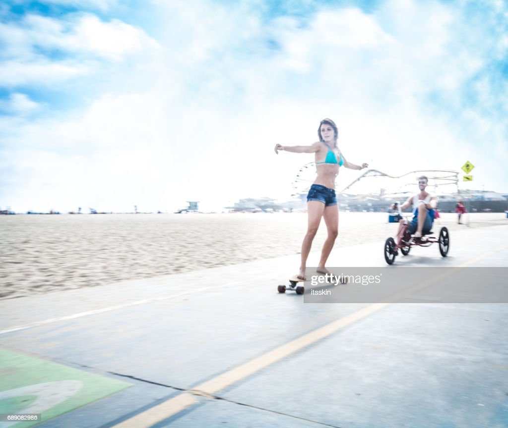 Couple in LA - riding three wheel bicycle and doing skateboarding : Stock Photo