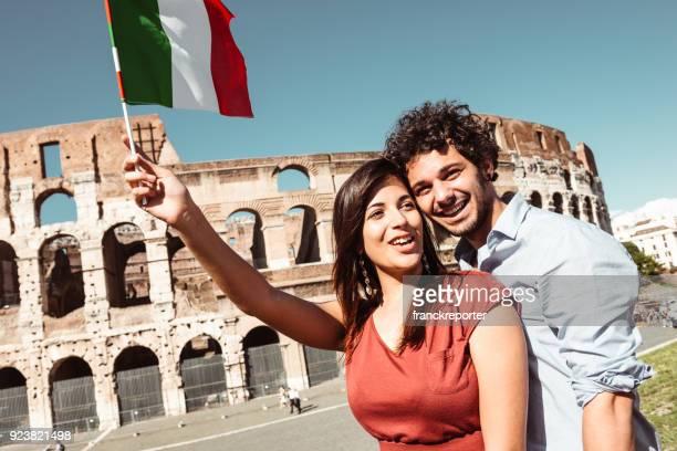 pareja en roma con la bandera en el coliseo - bandera italiana fotografías e imágenes de stock