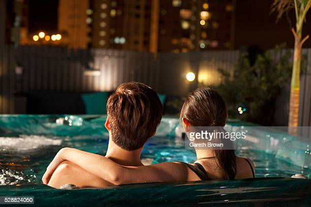 couple in rooftop hot-tub at night - hot tub stock pictures, royalty-free photos & images
