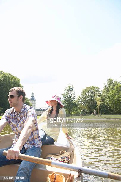 Couple in rowing boat, man rowing, woman relaxing