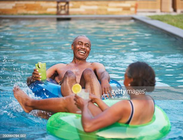Couple in rubber tube relaxing in pool, holding cocktail, laughing