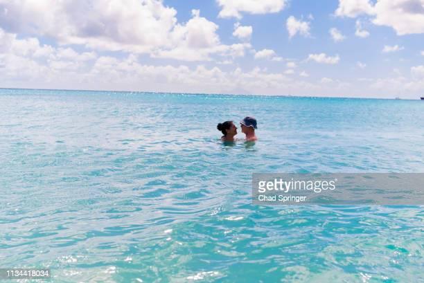 couple in sea, st maarten, netherlands - sint maarten caraïbisch eiland stockfoto's en -beelden