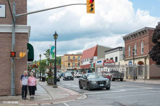 couple in senior age walk on the street of small town campbellford, ontario,  canada - severn river stock pictures, royalty-free photos & images