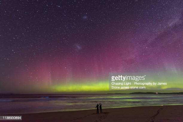a couple in silhouette dancing on a beach watching an incredible bright green display of the aurora australis or southern lights over a beach in tasmania with bright blue bioluminescence in the waves. - aurora australis stock pictures, royalty-free photos & images