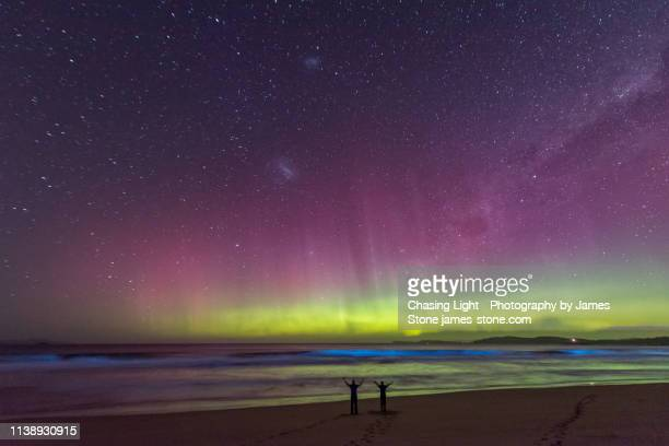 a couple in silhouette standing on a beach watching an incredible bright green display of the aurora australis or southern lights over a beach in tasmania with bright blue bioluminescence in the waves. - aurora australis stock pictures, royalty-free photos & images