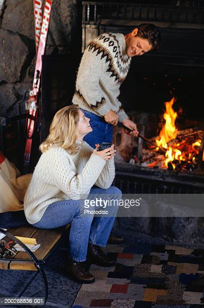 Couple in ski lodge by fireplace, man stoking fire