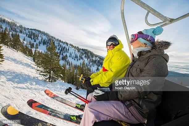 Couple in skiwear sitting on ski lift
