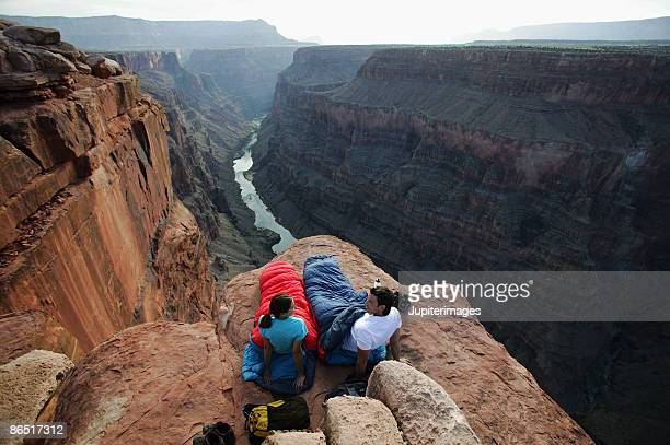 Couple in sleeping bags on canyon cliff