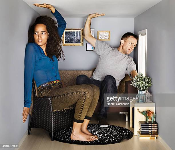 couple in small scale living room - trapped stock pictures, royalty-free photos & images