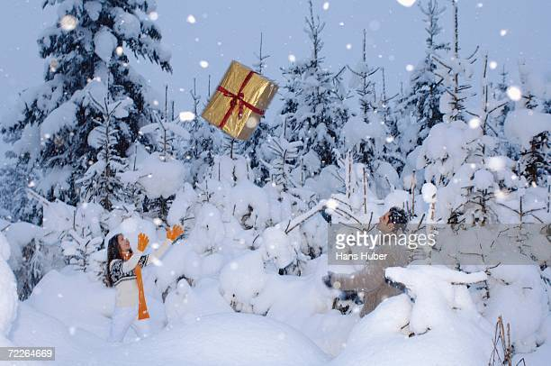 Young couple in snow, throwing present at each other, side view