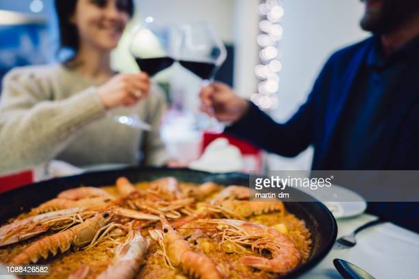 couple in spain celebrating valentine's day in traditional paella restaurant. - valencia spain stock pictures, royalty-free photos & images