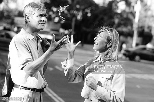 couple in street tossing car keys in air, (b&w) - homem pegando mulher imagens e fotografias de stock
