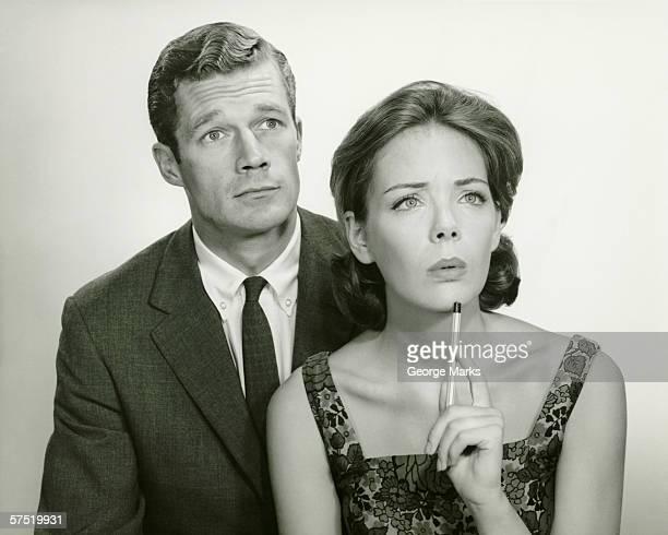 couple in studio, looking thoughtful, posing (b&w), portrait - 1950 stockfoto's en -beelden
