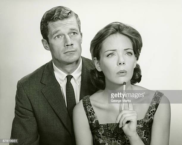 Couple in studio, looking thoughtful, posing (B&W), portrait