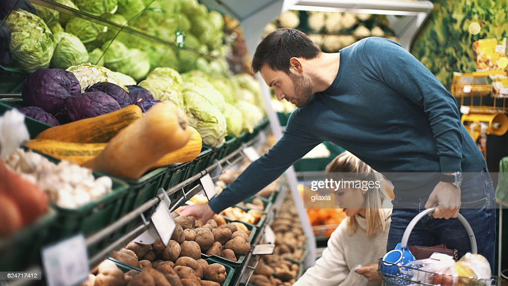 Couple in supermarket buying vegetables. : Stockfoto