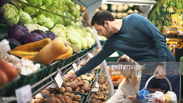 couple in supermarket buying vegetables. - convenience store stock photos and pictures