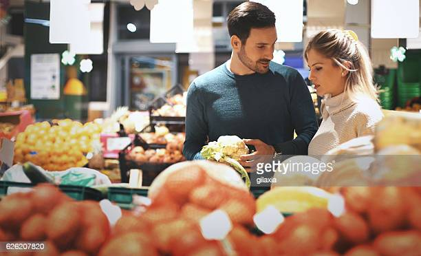 Couple in supermarket buying vegetables.