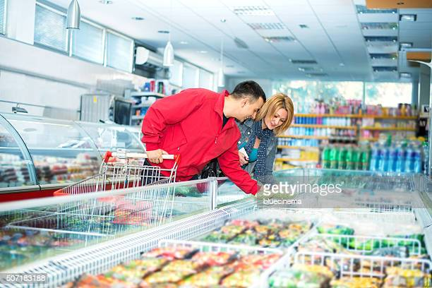 Couple in supermarket near frozen food