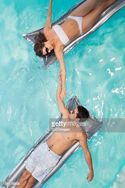 Couple in swimming pool lying on raft