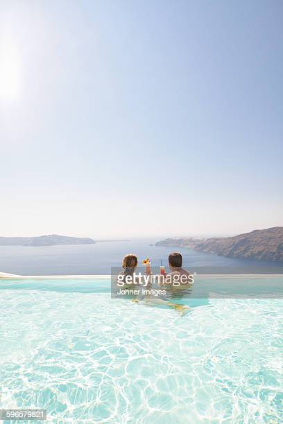 Couple in swimming-pool having cocktails