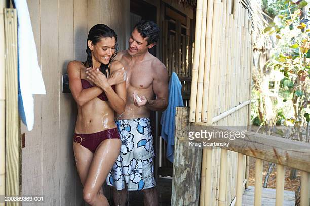 couple in swimsuits rinsing off in outdoor shower, smiling - pareja ducha fotografías e imágenes de stock