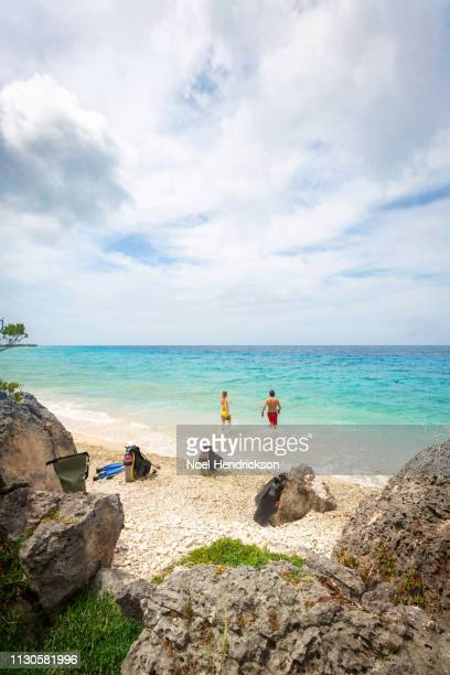 Couple in swimwear walking on the beach after scuba diving in the sea