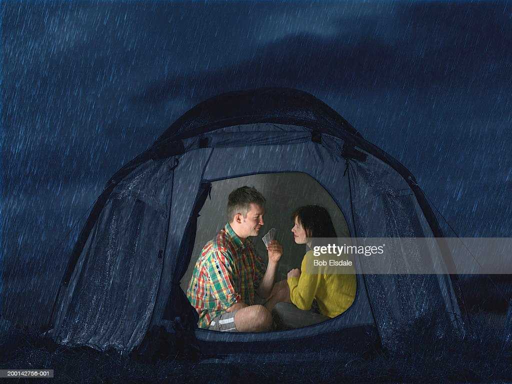 Couple in tent playing cards night  Stock Photo & Couple In Tent Playing Cards Night Stock Photo | Getty Images