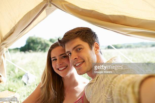 Couple in tent taking photo of themselves.